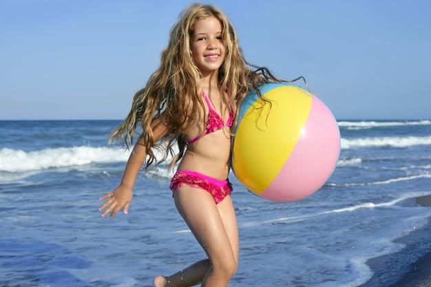 Plage petite fille balle colorée jouant en vacances
