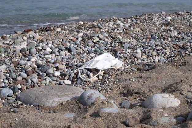 Plage sur la plage méditerranéenne avec poubelle sous forme de masque médical. déchets