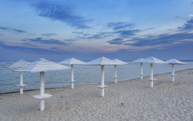 Plage propre et vide sur la mer adriatique, vue aérienne. parasols en bois pour se protéger du soleil.