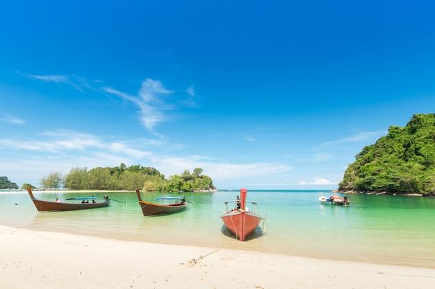 Plage de sable blanc et bateau à longue queue à l'île de kham-tok (koh-kam-tok)