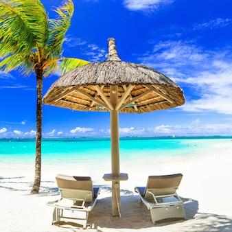 Plage de sable blanc avec chaises longues et parasol