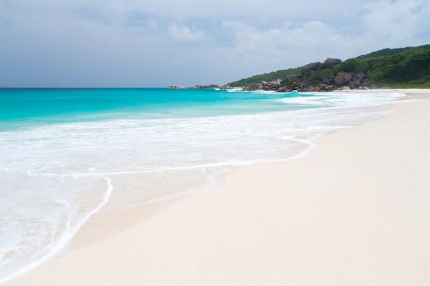 La plage de sable blanc et eau turquoise avec des vagues