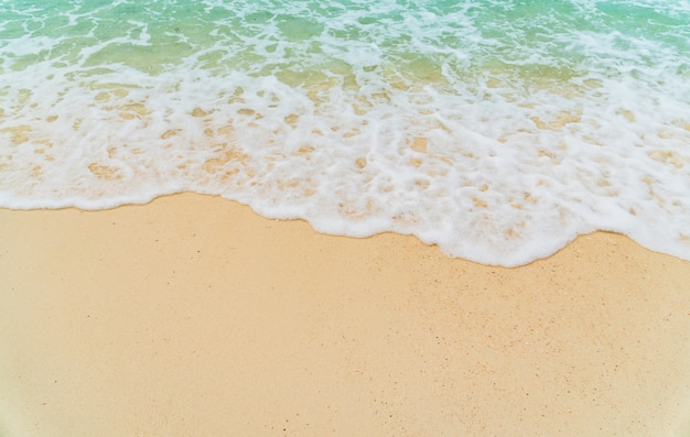 Plage de sable bord de mer avec vague bleue et fond d'été mousseux blanc, vue de dessus de plage aérienne au-dessus de la mer.