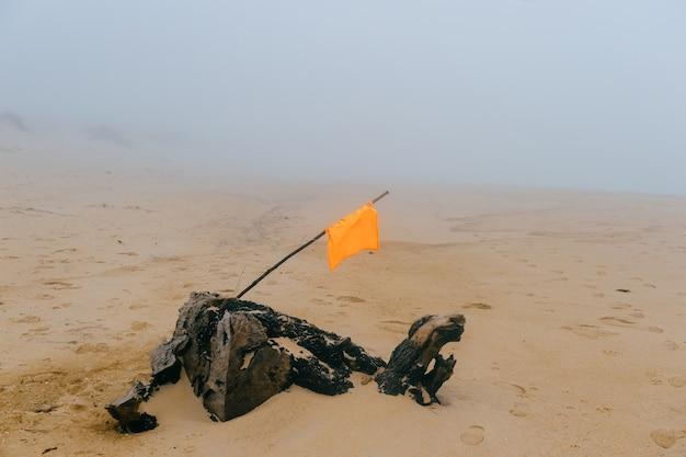 Plage de sable brumeux et brumeux avec drapeau dans le sable