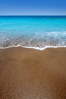 Plage de sable brun des îles canaries eau turquoise