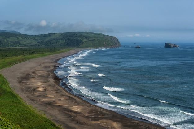 Plage de sable de couleur sombre presque noire de l'océan pacifique. les montagnes de pierre et l'herbe jaune sont sur un fond. ciel bleu clair.