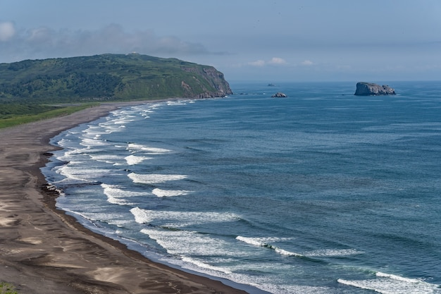 Plage de sable de couleur sombre presque noire de l'océan pacifique. les montagnes de pierre et l'herbe jaune sont sur un fond.