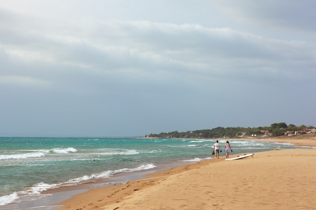 Plage de sable fin vue mer l'été, vagues en journée ensoleillée. vagues scintillantes sur la plage. deux adolescents marchent le long du rivage. concept de voyage et de vacances. plan global. espace de copie.