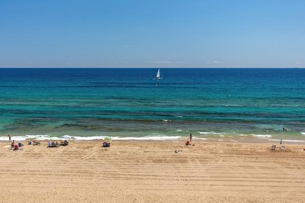 Plage de sable jaune, eau turquoise et ciel bleu ensoleillé. les touristes se reposant sur la plage et regardant la mer méditéranienne.