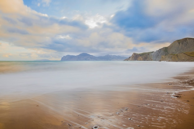 Plage de sable avec des montagnes en arrière-plan. les montagnes sont couvertes d'herbe et ont des falaises abruptes de la mer. le ciel est clair