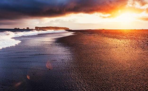 Plage de sable noir de reynisfjara en islande. montagnes reynisfyal