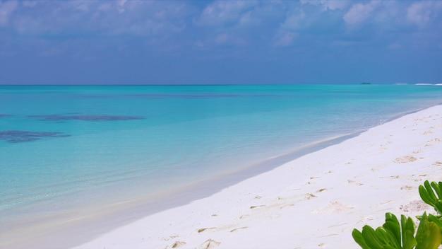 Plage de sable oblique par temps nuageux eau turquoise