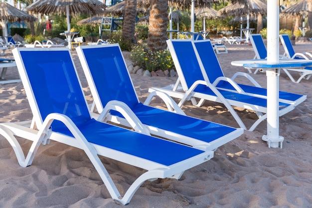 Plage de sable avec des palmiers avec une pergola en métal et des chaises longues en plastique