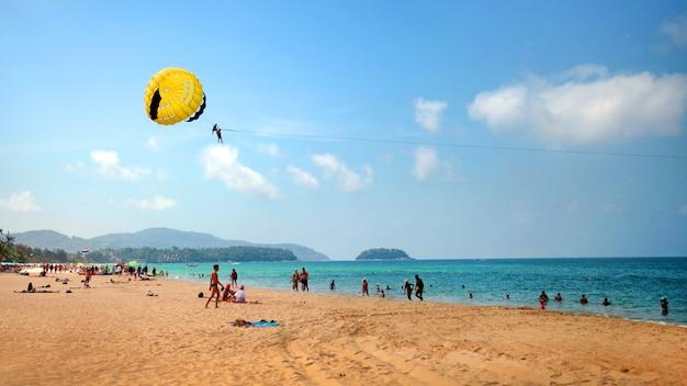 Plage de sable, parachutisme au-dessus de la mer par une journée ensoleillée, nuages légers dans le ciel bleu parachute ascensionnel