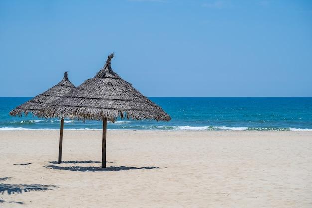 Plage de sable tropicale et eau de mer d'été avec ciel bleu et deux parasols de paille