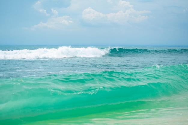 Une plage de sable tropicale idéale pour surfer sur l'océan. belle eau turquoise claire et vagues.