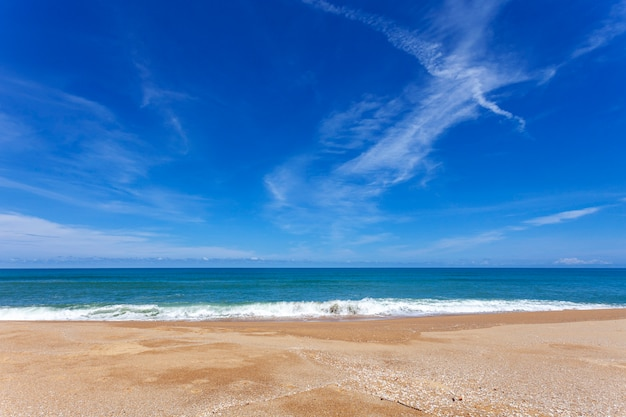 Plage de sable tropicale avec l'océan bleu et fond de ciel bleu