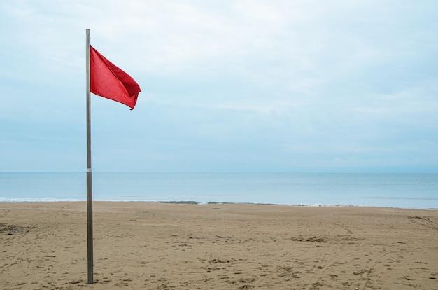 Plage de sable vide et drapeau de tempête rouge par temps nuageux.