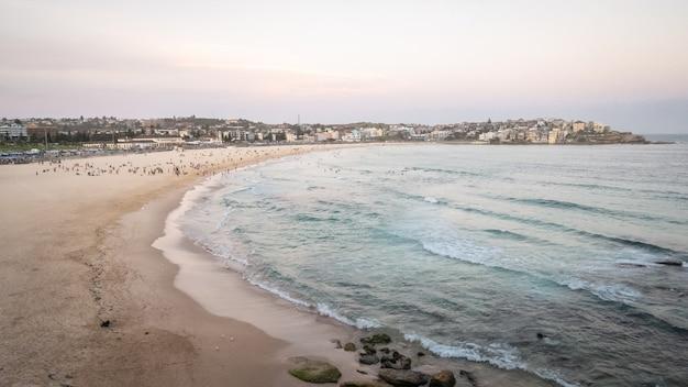 Plage de sable de la ville pendant le coucher du soleil tourné à bondi beach à sydney