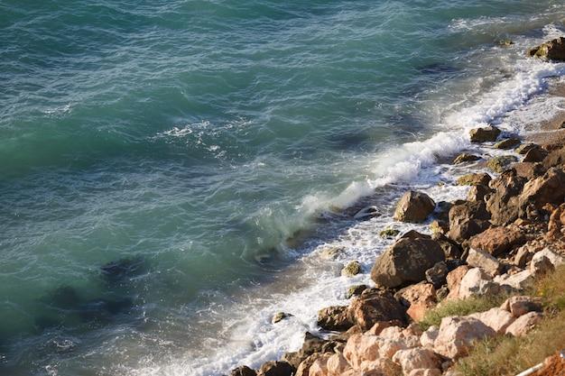 Plage sauvage aux pierres jaunes et mer limpide