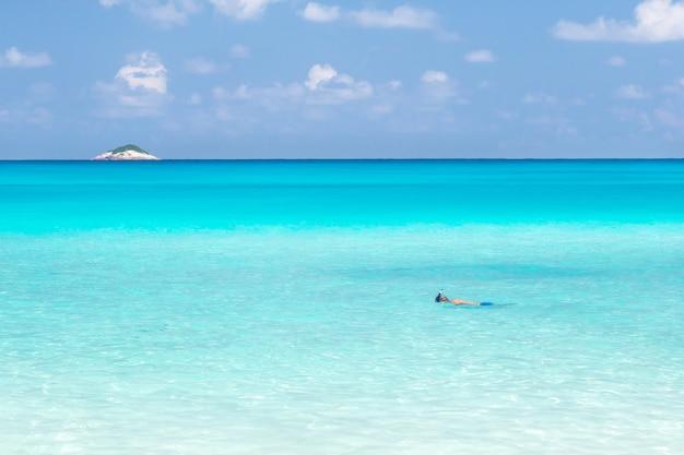 La plage des seychelles avec de l'eau bleue et des pierres