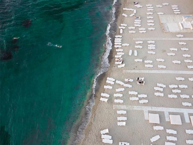 Plage et transats en bord de mer avec eau émeraude. vacances d'été au bord de la mer.