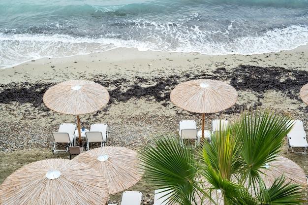 Plage avec transats, parasols sur la côte de la mer égée en grèce