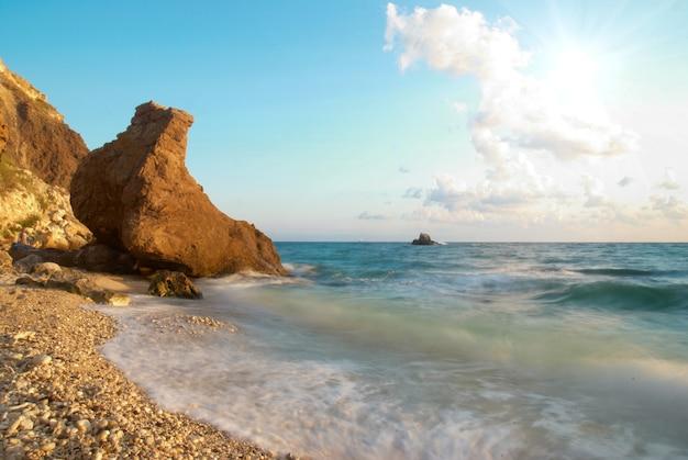 Plage tropicale au coucher du soleil avec de l'eau et des rochers.