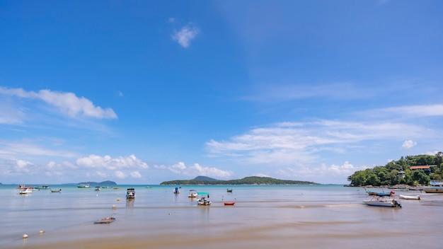 Plage tropicale avec des bateaux longtail dans le ciel bleu de la mer et des nuages blancs en saison estivale.