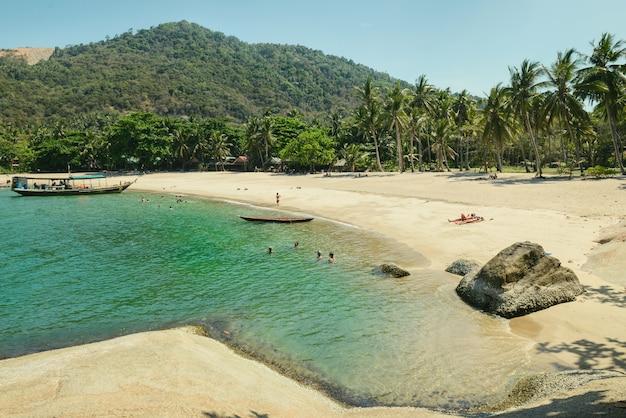 Plage tropicale avec cocotiers. les gens se détendent sur l'île en thaïlande. ciel bleu clair et mer calme