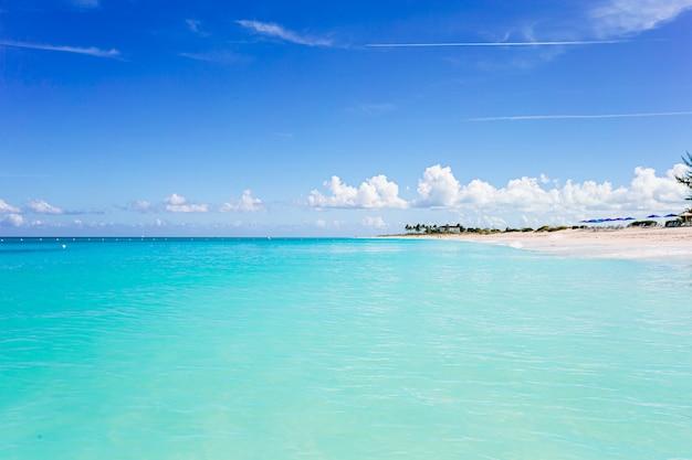 Plage tropicale idyllique dans les caraïbes avec sable blanc, eau de mer turquoise et ciel bleu