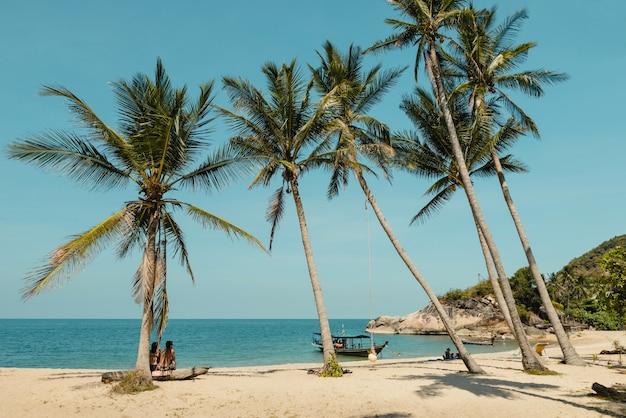 Plage tropicale avec palmiers coconat. les gens se détendent sur l'île en thaïlande. ciel bleu clair et mer calme