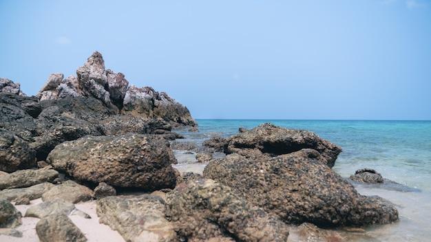 Plage tropicale, rocher et sable avec ciel bleu.