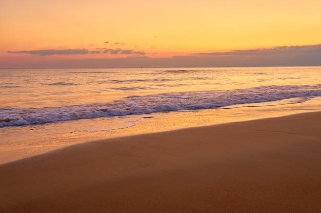 Plage tropicale de sable au coucher du soleil