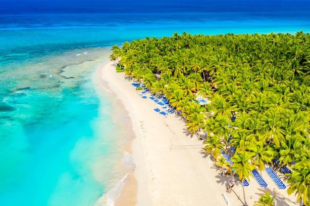 Plage tropicale de sable blanc avec cocotiers. vue aérienne de la côte idyllique de la mer turquoise. île de saona, république dominicaine.