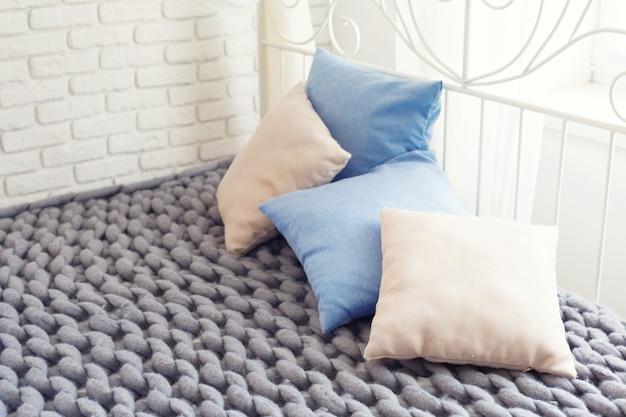 Plaid géant en maille grise avec oreillers