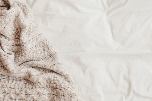 Plaid en laine sur un drap blanc
