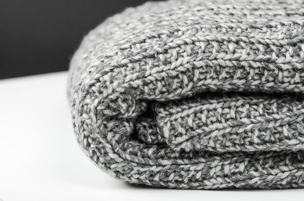 Plaid en laine grise, mensonge enroulé sur une table blanche. fermer.