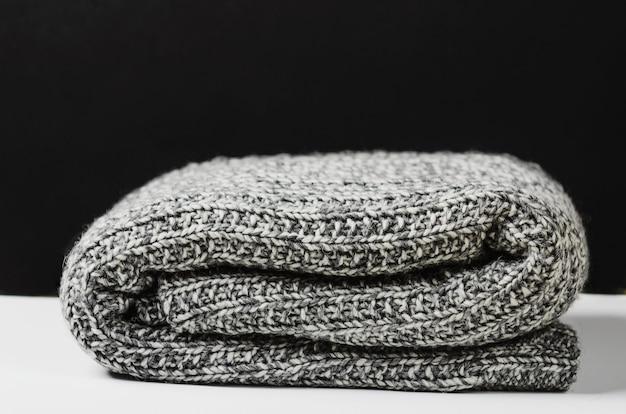 Plaid en laine grise, mensonge enroulé sur une table blanche.