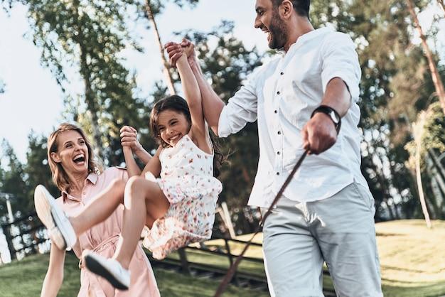 Plaisir en famille. mère et père balançant sa fille et souriant en marchant dans le parc
