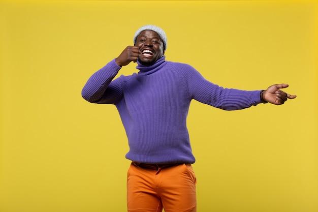 Plaisir de la vie. gentil jeune homme exprimant la positivité en se tenant debout sur fond jaune