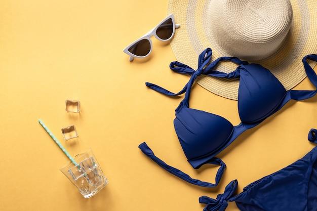 Plaisirs d'été et accessoires sur fond jaune. maillot de bain bleu, chapeau de paille et lunettes de soleil. image horizontale, place pour le texte