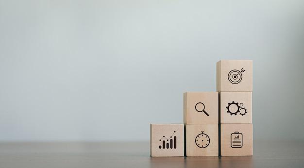 Plan d'action de stratégie commerciale en blocs de bois les objectifs des entrepreneurs tas de bois sur la table avec des icônes sur la stratégie commerciale et le plan d'action. espace de copie de concept de développement commercial