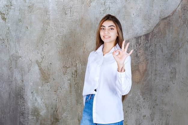 Plan d'une adorable fille aux cheveux longs posant devant la caméra et donnant un signe ok