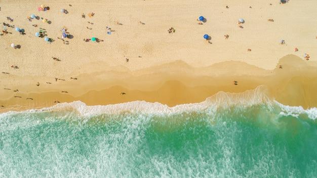 Plan aérien verrouillé des vagues déferlant sur le rivage. parasols colorés et personnes profitant de l'été.
