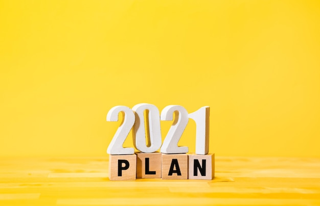 Plan d'affaires 2021 avec texte sur boîte en bois sur fond jaune.vision vers le succès