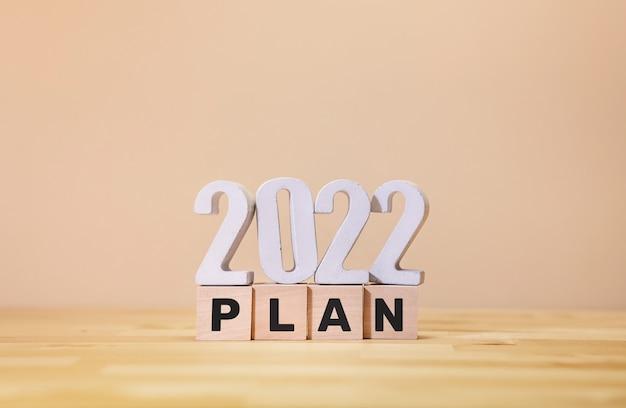 Plan d'affaires 2022 avec texte sur boîte en bois sur fond jaune.vision du succès