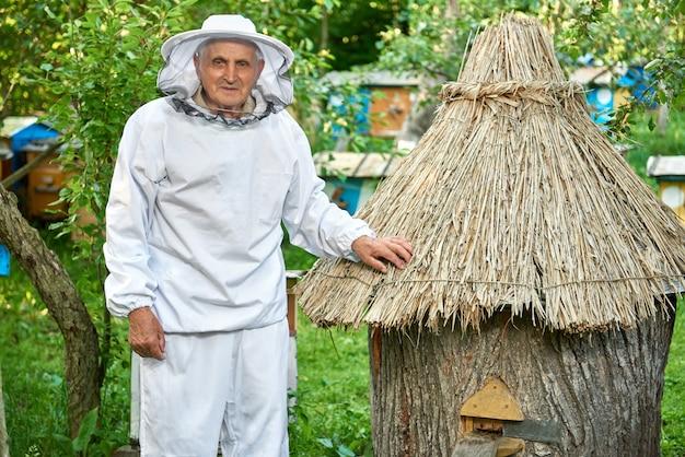 Plan d'un apiculteur de sexe masculin portant un costume d'apiculture posant à son rucher près de la ruche, fond, profession agricole, passe-temps, concept de retraite.