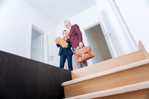 Plan de l'appartement. agent immobilier élégant et expérimenté montrant son riche plan d'appartement pour client tout en quittant une grande maison moderne