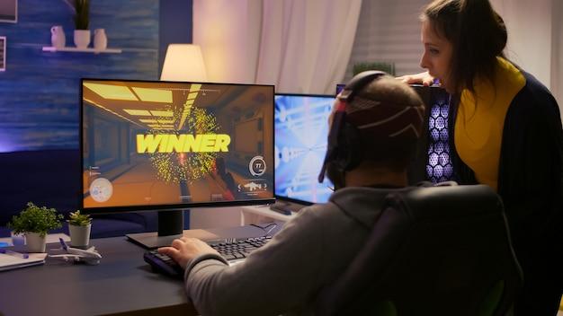 Plan arrière d'un couple excité, d'un joueur d'esport remportant un jeu vidéo de tournoi virtuel à l'aide d'un équipement rvb. homme gagnant jouant à la compétition de tir à la première personne en ligne avec un ordinateur professionnel puissant